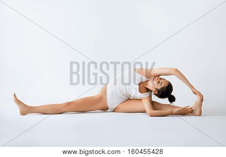 Young Woman Doing Yoga Asana Revolved Head To Knee Pose