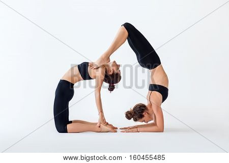 Two Young Women Doing Partner Yoga Asana Camel Pose And Scorpion