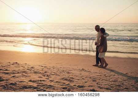 Senior Couple Strolling On The Beach At Sunset