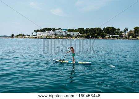 Man on stand up paddling in the Sea on a clear sunny day.