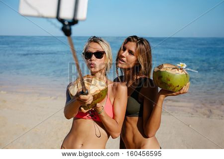 Two beautiful young women in bikini on the beach talking self portrait with smart phone on selfie stick. Female friends having fun on the beach with coconuts and taking pictures.