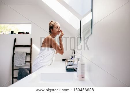 Young Woman Applying Cream On Her Face In Bathroom