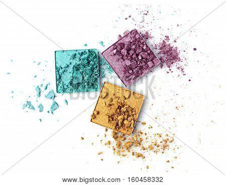 Crushed multicolored eyeshadows isolated on white background