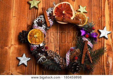 green colorful firry christmas wreath decorative with silver golden stars cone anise and cinnamon with dry orange on brown vintage wooden background