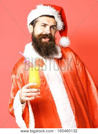 handsome bearded santa claus man with long beard on happy face holding glass of nonalcoholic cocktail in christmas or xmas sweater and new year hat on red studio background
