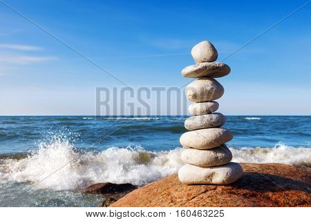 Concept of harmony and balance. high pyramid of white stones. Rock Zen in the background of the sea