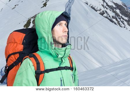 The mountaineer looks at the peak, standing against a winter mountain landscape.