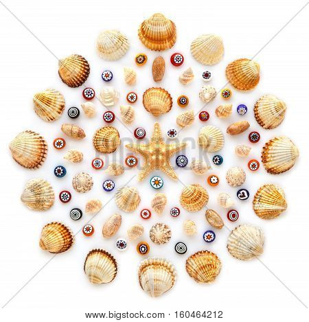 Round pattern of shells starfish and glass beads on white background. Flat lay top view