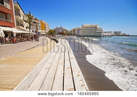 TENERIFE SPAIN - JUNE 11: Scenic view of some tourist walking on a Promenade in El Medano Beach on June 11 2015 in El Medano Canary Island Tenerife Spain
