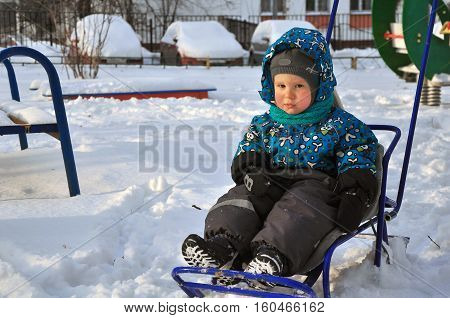 the offended little boy with pouted sits in the sledge on snow