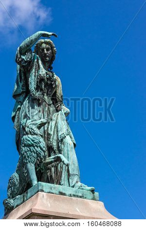 Inverness Scotland - June 1 2012: Closeup of greenish bronze Flora MacDonald statue shows the heroic lady and her dog against blue sky. No pedestal.
