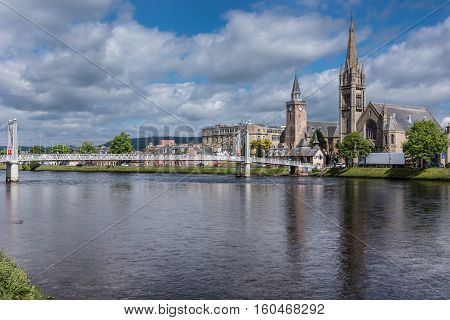 Inverness Scotland - June 1 2012: Wide combination photo of the Old High Church on the left and the Free Church of Scotland behind the Ness River with metallic Greig Street suspension bridge under blue sky with white clouds.