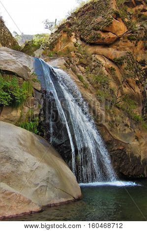 Long shot of a waterfall on the Cascadas del rio Colorado Trek close to Cafayate in Argentina South America poster