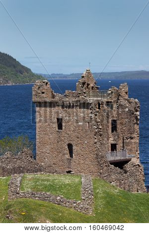 Loch Ness Scotland - June 2 2012: The ruins of the main tower and house of Urquhart Castle sit on a cliff looking over deep blue Loch Ness. Surrounding green hills. Light blue sky.