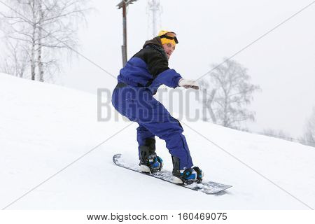 Snowboarder slides from the mountain. Sportsman on a snowboard