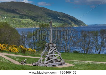 Loch Ness Scotland - June 2 2012: An ancient wooden gray catapult sits on the grounds of Urquhart Castle which sits on a green cliff looking over Loch Ness. Surrounding green hills. Light blue sky.