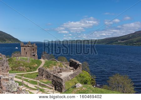 Loch Ness Scotland - June 2 2012: Shot of the wider deep blue Loch Ness with part of Urquhart Castle ruins in the foreground. Green surrounding hills. Light blue sky.