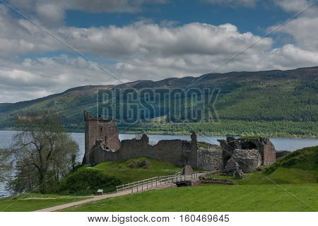 Loch Ness Scotland - June 2 2012: The ruins of Urquhart Castle on the green cliffs. Loch Ness visible in back. Green surrounding hills. Dark cloudy sky.
