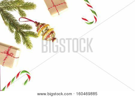 Christmas composition. Green fir twings, candy canes, Xmas gifts and decoration on white background. Top view, flat lay. Copy space for text. Winter holidays concept
