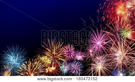 Multi-colored fireworks as a border on dark blue background ideal for New Year or other celebration events