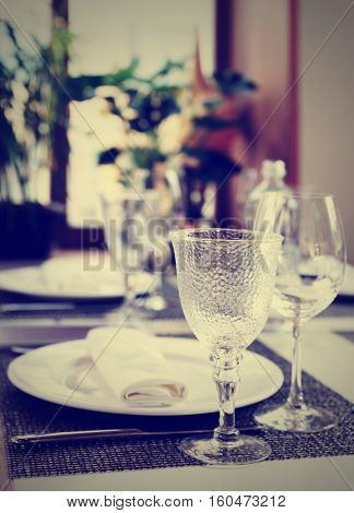 Place setting near the window in an expensive restaurant, toned image