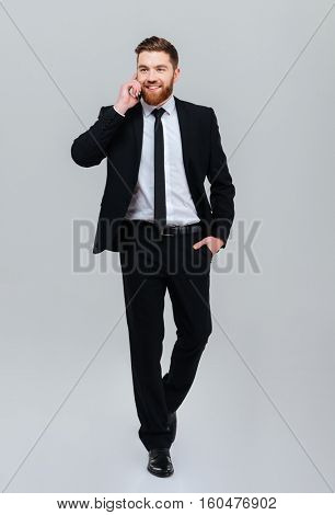 Full length young bearded business man in black suit moves with hand in pocket and talking at phone in studio. Isolated gray background