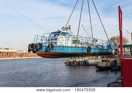 MOSCOW, RUSSIA - NOVEMBER 11, 2016: State Unitary Enterprise Mosvodostok performs recovery vessels on coastal winter parking. The ship hanging on chain slings cargo.