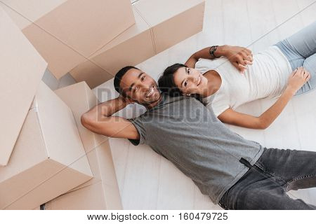 Happy couple lies on floor with unpacked boxes. Looking at camera.