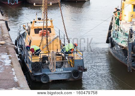 MOSCOW, RUSSIA - NOVEMBER 11, 2016: State Unitary Enterprise Mosvodostok performs recovery vessels on coastal winter parking. Two workers slingers hooked to the vehicle chain slings.