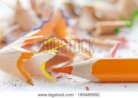 Sharpened orange pencil and wood shavings. Close up shot.
