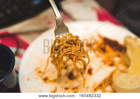 Fork full of sauce covered spaghetti close up