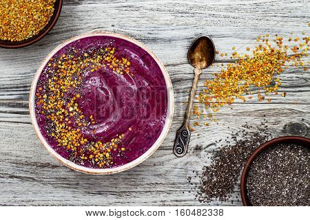 Acai breakfast superfoods smoothies bowl with chia seeds bee pollen toppings. Immune boosting anti inflammatory smoothie with turmeric honey and maca powder. Overhead top view flat lay copy space