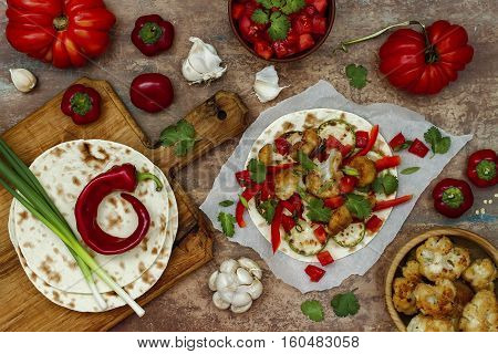 Spicy veggies tacos with roasted cauliflower zucchini and tomato salsa on rustic wooden cutting board. Preparing healthy lunch vegetarian snack. Top view overhead flat lay