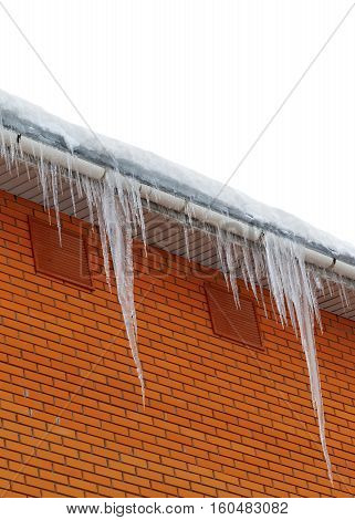 Snow-covered roof with icicles. Isolated on white background with copy space