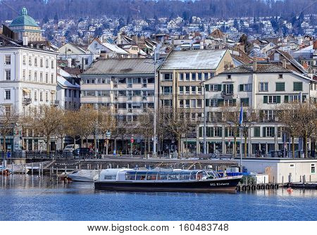 Zurich, Switzerland - 18 January, 2016: boats on the Limmat river, people on its embankment, old town buildings in the background. Zurich is the largest city in Switzerland and the capital of the Swiss Canton of Zurich.