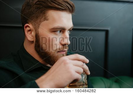 Image of handsome man sitting in armchair and drinking whiskey . Look aside.