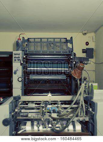 Offset printing machine in basement room. Professional machine