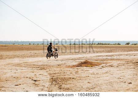 Man is kicking up dust as he rides his motorcycle through the desert