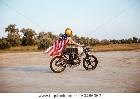 Side view of a young brutal man in golden helmet and american flag cape driving retro motorcycle