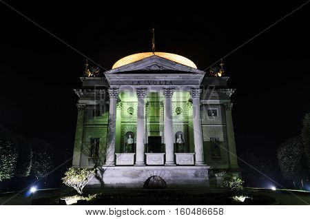 main entrance of the Volta Temple at night in the center of Como city Italy