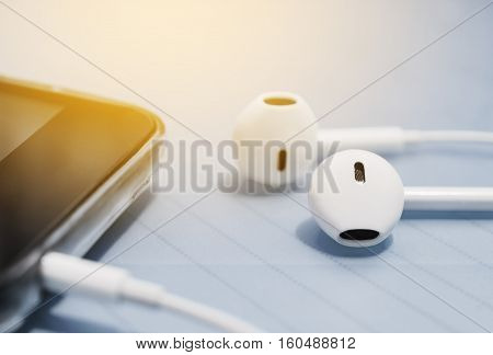 Ear phone into smart phone mobile on blurred background filter color style