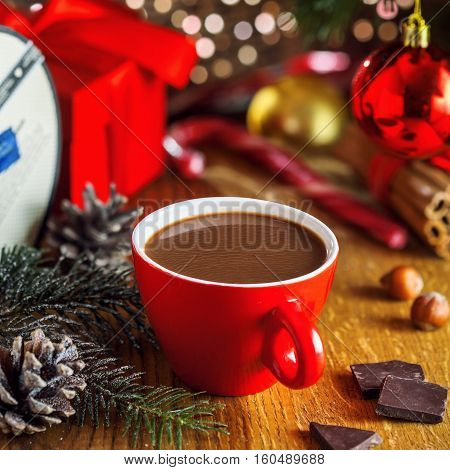 Traditional Christmassy hot chocolate beverage and gift boxes under Christmas tree. Tasty cocoa drink.