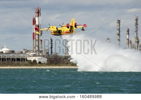 Marseille, France - March 30, 2015: Canadair, water bomber plane in training in the harbor near a petrochemical industrial site