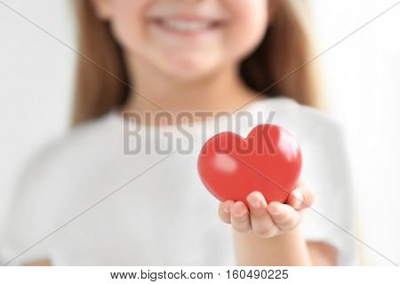 Little girl holding heart in her hand