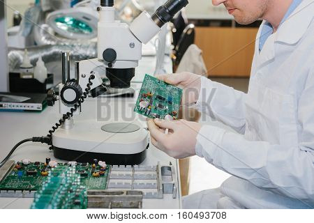 Microchip production factory. Technological process. Assembling the board. Computer expert. Manufacturing. Engineering. Chip. Professional. Technician.
