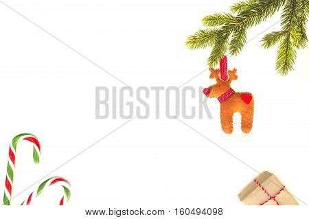 Christmas composition. Green fir twings, candy canes, Xmas gifts and handmade felt decoration on white background. Top view, flat lay. Copy space for text. Winter holidays concept