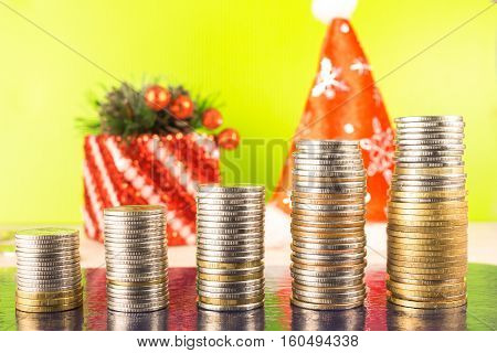 Business Finance and money concept. Five growing stacks count coins. Standing on wooden table on bright background. New year cap of Santa Claus spruce and gift for Christmas