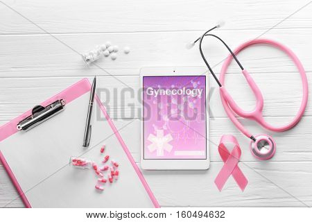 Tablet with word GYNECOLOGY, ribbon and stethoscope on light wooden background