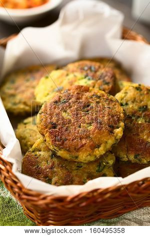 Zucchini couscous and parsley fritters in basket photographed with natural light (Selective Focus Focus in the middle of the top fritter)