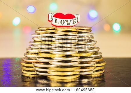 Pyramid of coins with the inscription love on top. Blurry bright background with lights on a dark table